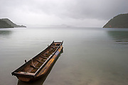 A boat on a misty day when the water is calm at Lugu Lake, Yunnan, China. Lugu Lake is located in the North West Yunnan plateau in the centre of Ninglang Yi Autonomous County in the Peoples Republic of China.