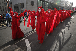 © Licensed to London News Pictures. 09/10/2019. London, UK. Extinction Rebellion Red Brigade activists process along Victoria Street during a third day of protests in central London. The climate change group intend to blockade the Westminster area for two weeks to demand that the government takes immediate and decisive action on climate change. Photo credit: Peter Macdiarmid/LNP