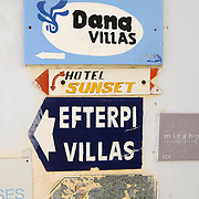 Signs of Santorini villas and hotel on the whitewashed wall in Firostefani