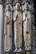 West Facade, Central Portal - Left Jamb Figures c. 1145. Cathedral of Chartres, France . Gothic statues on the left jamb of the central portal. All have haloes. The leftmost is a crowned woman whose hair is in long plaits; she holds a book. The central figure is a bearded man in a cap that resembles the ones worn by other jamb figures and by figures in the tympanum of the right portal. He holds an unidentified object. The figure nearest the portal is a bearded man holding a scroll and raising one hand- palm outwards- towards the viewer. A UNESCO World Heritage Site. . .<br /> <br /> Visit our MEDIEVAL ART PHOTO COLLECTIONS for more   photos  to download or buy as prints https://funkystock.photoshelter.com/gallery-collection/Medieval-Middle-Ages-Art-Artefacts-Antiquities-Pictures-Images-of/C0000YpKXiAHnG2k