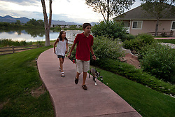 "Santiago Gonzalez, 13, walks the family dog Leo, with his sister Andrea, Littleton, Colo., Aug. 29, 2011. Gonzalez is a full-time college student at the Colorado School of Mines, an engineering university. He wakes up at 5:30 a.m. every morning during the academic semester to develop iPad and iPhone applications in a programming language called Objective C, which he learned from a textbook when he was 9 years old. That textbook and 86 similar volumes including Applied Finite Mathematics, Infinity in Your Pocket, Programming in C++ and Dictionary of Physics, sit in a glass-fronted bookcase opposite his bed. ""Exceptionally gifted"" is the commonly used phrase for kids as smart as Gonzalez."