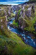 Fjaðrárgljúfur is a canyon in south east Iceland which is up to 100 m deep and about 2 kilometers long, with the Fjaðrá river flowing through it .The canyon has steep walls and winding water.