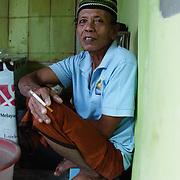 A man smokes a cigarette on the streets of Komodo. Komodo Island, Indonesia.