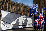 Pro-EU campaigners stand with EU flags opposite parliament during the continuing protest against Brexit, on 19th February 2019, in London, England.