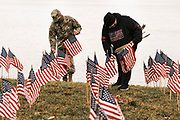 10 SEPTEMBER 2020 - DES MOINES, IOWA: US Air Force A1C REEVES, left, and TRACY STAMPER set out American flags along the shore of Gray's Lake. About 25 volunteers braved cold and rainy weather Thursday to line the west end of Gray's Lake in Des Moines with American flags. The display of flags was a part of an annual event called the 9/11 Tribute Trail. About 3,000 flags were set out in memorial of the 3,000 people killed in the 9/11 terrorist attacks.     PHOTO BY JACK KURTZ