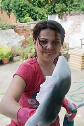 Eastern European working as cleaner washing office windows,
