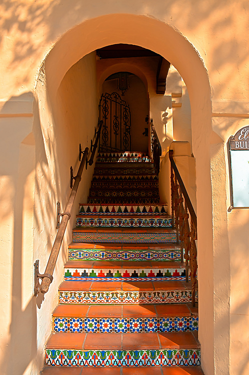 About the Subject: Carmel-by-the-Sea exudes art, quaintness and endless individual details - a treasure trove for painters and photographers. Spanish/Mexican influences are abundant throughout the commercial and residential enclaves. <br /> <br /> About the Photo: The arched staircase with adobe walls and tiled steps leads to an iron gate at the top and offices. Late afternoon sun dapples the walls and casts the shadow of trees and a street lamp.While a human eye can  simultaneously see both the bright sun-lit portions and the considerably darker interior and top of the stairs, the camera can not. This image was constructed from five photographs with different exposures. The over-exposed captured the dark areas and the under-exposed the bright areas. Combined, the exposure is balanced overall into a single image.