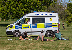 © Licensed to London News Pictures. 19/04/2020. London, UK. Three members of the public exercise as Police vans patrol Primrose Hill enforcing lockdown rules on social distancing and exercise as Ministers urge councils to keep parks open to the public during lockdown. Photo credit: Alex Lentati/LNP