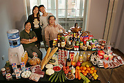 (MODEL RELEASED IMAGE).The Dong family in the living room of their one-bedroom apartment in Beijing, China, with a week's worth of food. Seated by the table are Dong Li, 39, and his mother, Zhang Liying, 58. Behind them stand Li's wife, Guo Yongmei, 38, and their son, Dong Yan, 13. The Dong family is one of the thirty families featured in the book Hungry Planet: What the World Eats (p. 74).