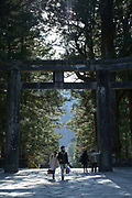 A couple walk holding hands through Tori gate to the Toshogu Shrine. Nikko, Japan
