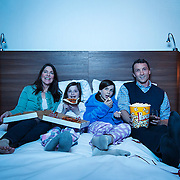 Advertising photography for Hotel Elan.<br /> Family sharing pizza and popcorn on bed while watching TV in a hotel.<br /> Hair & Make-up Stylist: Shannon Payne<br /> Art Director: Judith Aldama<br /> Photography: Brett Gilmour