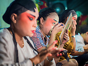 """14 MAY 2015 - BANGKOK, THAILAND:  Chinese opera performers put on their makeup before going on stage at the Pek Leng Keng Mangkorn Khiew Shrine in the Khlong Toey slum in Bangkok. Chinese opera was once very popular in Thailand, where it is called """"Ngiew."""" It is usually performed in the Teochew language. Millions of Chinese emigrated to Thailand (then Siam) in the 18th and 19th centuries and brought their culture with them. Recently the popularity of ngiew has faded as people turn to performances of opera on DVD or movies. There are still as many 30 Chinese opera troupes left in Bangkok and its environs. They are especially busy during Chinese New Year and Chinese holiday when they travel from Chinese temple to Chinese temple performing on stages they put up in streets near the temple, sometimes sleeping on hammocks they sling under their stage. Most of the Chinese operas from Bangkok travel to Malaysia for Ghost Month, leaving just a few to perform in Bangkok.      PHOTO BY JACK KURTZ"""