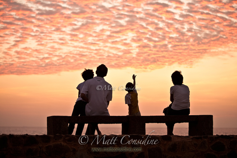 A family watches a fabulous sunset from the ramparts of the old fort.<br /> (Photo by Matt Considine - Images of Asia Collection)