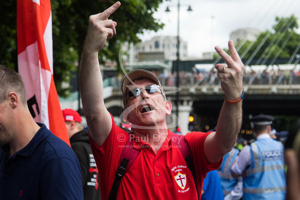 London, June 24th 2017. Anti-fascist protesters counter demonstrate against a march to Parliament by the far right anti-Islamist English Defence League. PICTURED: A member of the EDL makes obscene gestures at the antifascist 100 yards away.
