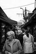 People walk down a small pedestrian street in Baščaršija, the old bazaar and cultural center of Sarajevo, Bosnia and Herzegovina