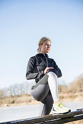 Woman with headphones doing stretching