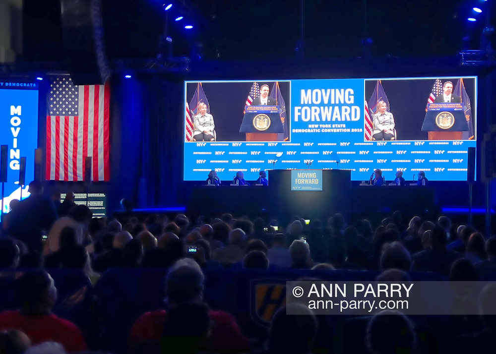 Hempstead, New York, USA. May 23, 2018. Before Hillary Clinton comes on stage to make Keynote Address, photos of Clinton's political career, including one with Governor Andrew Cuomo with her on stage, are on gigantic screen on stage, during Day 1 of New York State Democratic Convention, held at Hofstra University on Long Island.