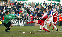 Photo: Chris Ratcliffe.<br />Colchester United v Southend United. Coca Cola League 1. 04/03/2006.<br />Freddie Eastwood (far right) watches the ball squeeze past his team mate Mark Gower and Colchester keeper Aidan Davison for Southend's opening goal.
