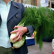 A woman carrying two fennel bulbs at Edinburgh Farmers Market, Scotland