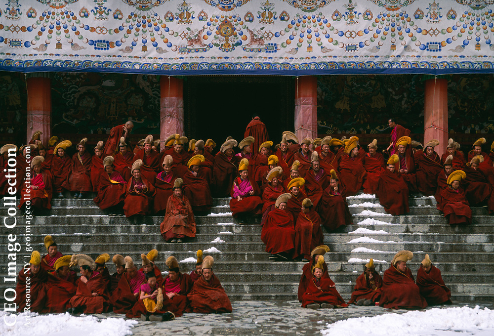 """In the chill of the early morning, monks gather on the steps of Labrang Monastery, awaiting prayers and their only meal of the day — sampa, made with yak butter tea. """"They have also immense Monasteries and Abbeys, some of them as big as a small town, with more than 2000 monks in a single abbey. These monks dress more decently than the rest of the people and have the head and beard shaven."""" The Travels of Marco Polo, Vol 1, Book 1, Ch 61. Gansu, China"""