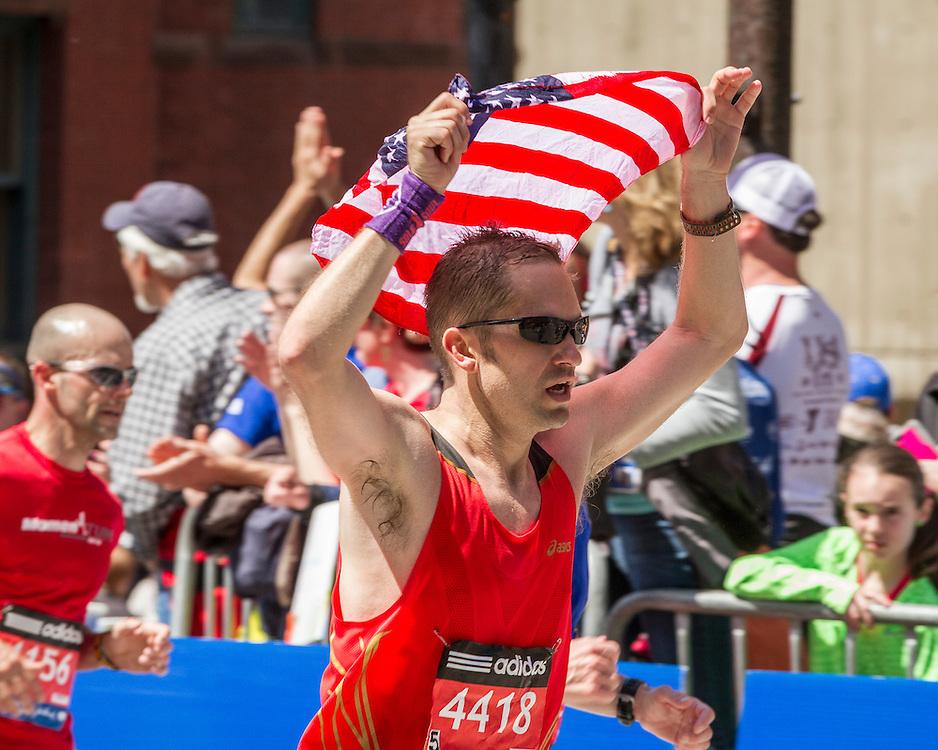 2014 Boston Marathon: runner with American flag heading for the finish line