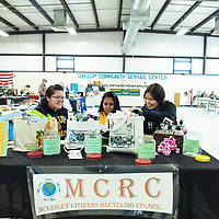 Gallup High School Key Club members Brianna Torres, 18, left, Tanisha Patel, 17, at the center, and Devin Begay, 18, right, finish the set up of their table Gallup Community Service Center for America Recycles Day, on Saturday in Gallup.