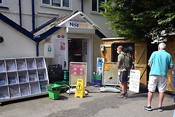 Social distancing in place outside Manorbier Stores, Pembrokeshire, South Wales during Covid pandemic, July 2021