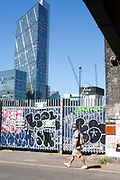 Pedestrians walk through graffiti on the streets in Shoreditch, London. In the background are the towers of the City of London