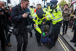 London, UK. 16 October, 2019. Metropolitan Police officers arrest Guardian journalist and environmental campaigner George Monbiot under Section 14 of the Public Order Act 1986 after he, Green Party co-leader Jonathan Bartley and a group of climate activists from Extinction Rebellion sat down in Whitehall following a People's Assembly in Trafalgar Square as part of a protest against the use by the Metropolitan Police of Section 14 so as to prohibit entirely Extinction Rebellion Autumn Uprising protests throughout the capital.