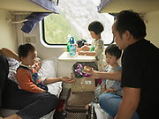 Mother and son with his 3 kids share a snack. They are returning home to Lanzhou after spending holiday with relatives in Xian. Life in the sleeping compartments in the train from Hong Kong to Urumqi, Xinjiang.