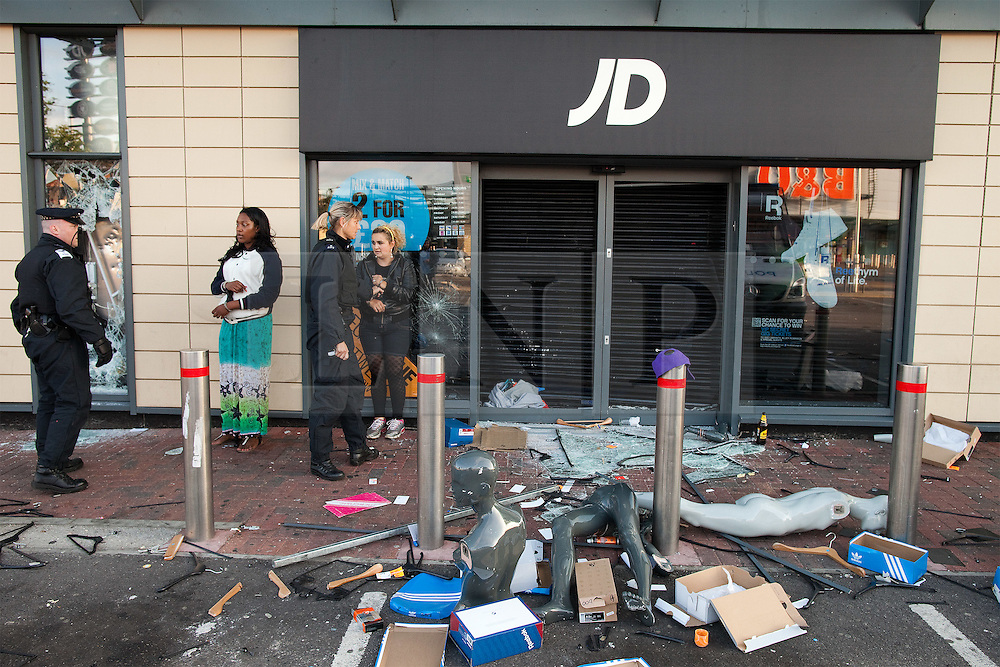 © Licensed to London News Pictures. 07/08/2011. Tottenham, UK. Police arrest looters found inside JD Sports at Tottenham Retail Park. Riots spread from Tottenham High Road and looters raided shops. Looters continued to rob from the store, even after sunrise. Looters struggled to escape, even after they were cuffed and police had to keep other people back as they arrested the looters. Photo credit : Joel Goodman/LNP