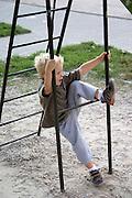 Boy age 3 climbing on park slide support structure. Balucki District Lodz Central Poland