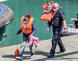© Licensed to London News Pictures. 20/07/2021. Dover, UK. A migrant family is escorted by a Border Force officer as they are brought ashore at Dover Harbour in Kent after crossing the English Channel. It is being reported that at least 430 migrants crossed the English Channel to the UK on Monday, a new single day record. Photo credit: Stuart Brock/LNP