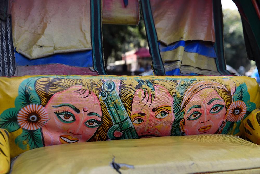 Three faces on the empty backseat of bicycle rickshaw in Dhaka, Bangladesh.
