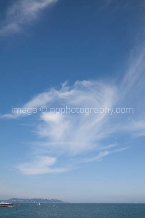 View from Dun Laoghaire of Dublin Bay and Howth Ireland with swirling clouds in the blue sky