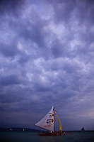 Sailboat in late afternoon dramatic skies off Boracay Island, Philippines.
