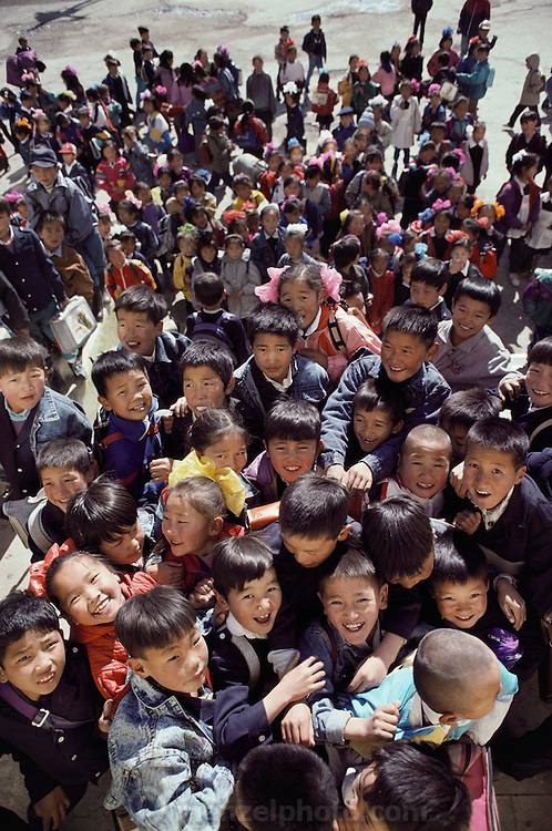 Schoolchildren jam the doorway of their school before their classrooms open in the morning. Ulaanbaatar, Mongolia. Material World Project.