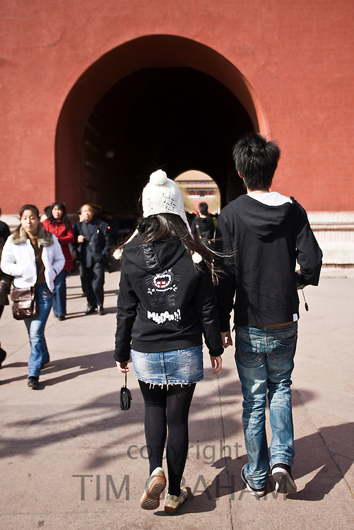 Young Chinese couple in modern casual western clothes visit the Forbidden City, Beijing, China