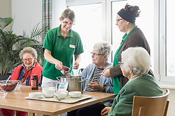 Nurses preparing dessert with senior residents in rest home
