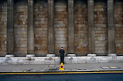 Beneath the giant, solid pillars of the Bank of England in the heart of London's financial district - the ancient Square Mile - a man dressed in a traditional pinstripe suit has stopped to make a phone call or check for messages. Halting his journey along this street he has opted to stand in line with a traffic no waiting cone and also near double-yellow lines that restrict parking or stopping. Without the cone or lines this scene would otherwise be without colour - the columns of this financial institution and the pavement (sidewalk) are drab - so the welcome yellow gives this picture more interest. We only see the man from the rear view and so he remains anonymous, a small person set against the scale of a large-scale financial landscape..