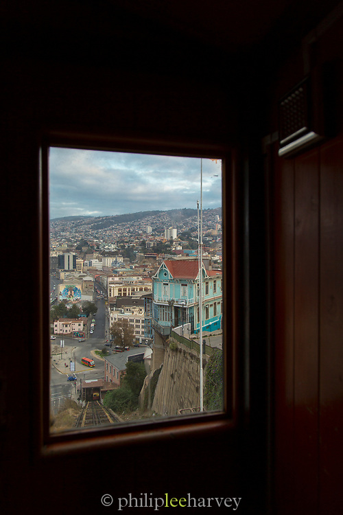Cityscape with streets and buildings seen through window of cable car, of Valparaiso, Chile