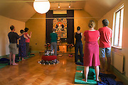 Buddhists meditate before silent meditation for 30 minutes in their Shrine Room at the Rivendell Buddhist Retreat Centre.
