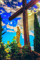 """""""Mother Mary under the Cross - the Convent of cells Cortona""""… <br /> <br /> Known as Le Celle, this Franciscan hermitage is just five miles from Cortona at the foot of Mount Sant' Egidio. In 1211 St. Francis, along with a few of his followers, built the first nine cells of the hermitage and the place has taken the name of Celle ever since. Inside the tiny cell belonging to St. Francis is a tiny window, the bed on which he slept, his desk, and a painting of the Madonna and Child where he prayed. The Hermitage invokes a peaceful atmosphere of spirituality and solitude, yet it is vibrant with religious life. Currently, the hermitage is inhabited by seven friars who continue to practice the teachings of St. Francis. I found Le Celle to be one of the pleasant surprises in and around Cortona. The tiny cells built into the side of the mountain with a stream descending along the structural edge create a surreal and picturesque vision of Saint Francis's image of God and nature. The convent can offer lodgings to those contemplating a vocational life. As I was exiting through the gates of the Convent, I noticed atop the embankment of the single dirt road leading there… a statue of Mother Mary. She stood majestically evoking a serene peacefulness over the Convent, its pilgrims, and visitors. The Madonna had rosaries swaying from her hand, and about 10 feet away stood a Cross surrounded by blooming roses. My mission was to capture a photograph containing all the elements of Mary, the Cross, roses, the famous Cypress trees of Italy, and the dramatic blue skies…it took a very creative epiphany or perhaps a miracle. I knelt on the edge of the rocky dirt road below the embankment as if I was in a fox hole, and peering upward, was able to contain all the elements in the frame of the image. Surprisingly to me, it worked, and the statue of the Madonna grew a distinct but faint smile watching the antics of a silly but grateful photographer."""