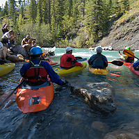 A photography class shoots kayakers wave surfing on the Kananaskis River in the Canadian Rockies near Calgary, Alberta.