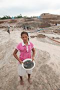 Yanti (22 years old). She stopped school at age 12 to work in the mine. . <br /> The tin ore she found is kept in a bowl. <br /> Illegal tin mine in Batako, Tunghin. Bangka Island (Indonesia) is devastated by illegal tin mines. The demand for tin has increased due to its use in smart phones and tablets.<br /> <br /> Yanti (22 ans). A arreté l'ecole a l'age de 12 ans. Pour se consacrer à la recherche d'étain. <br /> Mine d'étain illégale à Batako - Tunghin. <br /> L'île de Bangka (Indonésie) est dévastée par des mines d'étain sauvages. la demande de l'étain a explosé à cause de son utilisation dans les smartphones et tablettes.