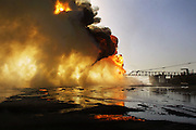"""Firefighters from the KWWK (Kuwait Wild Well Killers) attempt to extinguish an oil fire in the Rumaila Oil Field by guiding a """"stinger"""" that will pump drilling mud into the flaming well. A """"stinger"""" is a tapered pipe on the end of a long steel boom controlled by a bulldozer. Drilling mud, under high pressure, is pumped through the stinger into the well, stopping the flow of oil and gas. Many of the wells are 10,000 feet deep and produce huge volumes of oil and gas under tremendous pressure, which makes capping them difficult and dangerous. Rumaila, Iraq. Rumaila is also spelled Rumeilah."""