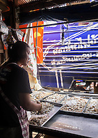 MAE KLONG - TAHILAND - CIRCA SEPTEMBER 2014: Merchant in the stalls of the Maeklong Railway Market