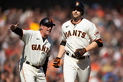 San Francisco Giants pinch hitter Austin Slater (13) gets a congratulatory handshake from third base coach Ron Wotus after hitting a solo home run off San Diego Padres pitcher Ross Detweiler during the sixth inning of a baseball game, Saturday, Oct. 2, 2021, in San Francisco. (AP Photo/D. Ross Cameron)