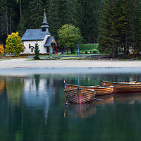 Reflection of small church and boats in the calm, peaceful waters of Lago di Braies early in the morning in Italy's Dolomites
