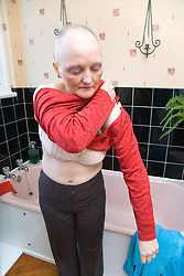 Woman who has had a mastectomy; the removal of a breast in response to breast cancer; and also hair loss as a result of chemotherapy treatment; getting dressed in her bathroom,